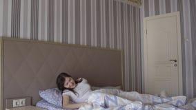 La bella donna castana sveglia nel suo letto video d archivio