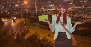 La bella donna che gesturing e che tiene la borsa verde con la borsa dell'imbracatura che sta contro la strada dentro si illumina fotografia stock libera da diritti
