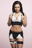 La bella donna che posa nell'domestiche succinte uniforma Fotografia Stock