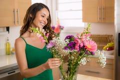 La bella donna che sistema i fiori ha selezionato dal suo giardino a casa felice ed allegro Immagini Stock