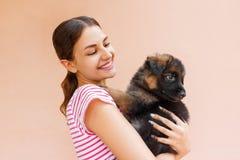 La bella donna che tiene e che esamina il ` nero s del cucciolo osserva fotografia stock libera da diritti