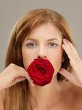 La bella donna che tiene il colore rosso è aumentato in bocca Immagini Stock Libere da Diritti