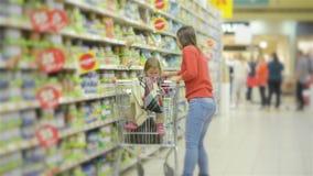 La bella donna con acquisto della figlia del bambino nel supermercato, giovane madre sceglie l'alimento per il loro bambino nel m archivi video