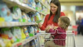 La bella donna con acquisto della figlia del bambino nel supermercato, giovane madre sceglie l'alimento per il loro bambino nel m video d archivio