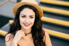 La bella donna con capelli scuri, il sorriso affascinante e splendere osserva il cappello di paglia d'uso mentre si siede alle sc fotografie stock libere da diritti