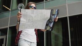 La bella donna con i vetri bollati e l'abbigliamento casual che esplorano la città tracciano con la lente d'ingrandimento archivi video
