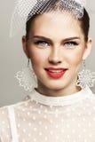 La bella donna con il cappello alla moda ed il bianco elegante ha punteggiato la blusa che guarda in avanti Immagine Stock