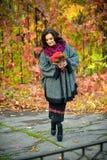 La bella donna con il crollo osserva nel parco di autunno Fotografie Stock