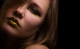 La bella donna con il nero e l'eye-liner dell'oro preparano l'esame Fotografia Stock