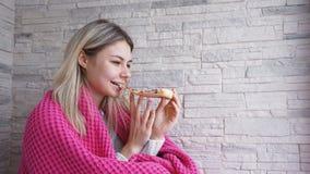 La bella donna con il plaid rosa tiene una fetta di pizza in sua mano e la mangia fotografia stock