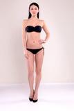 La bella donna con l'ente perfetto, con capelli diritti scuri porta il bikini nero fotografia stock libera da diritti