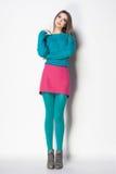 La bella donna con le gambe lunghe ha vestito la posa elegante Fotografia Stock