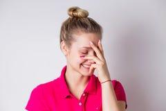 La bella donna con pelle pulita, risate naturali di trucco, sorride e copre il suo fronte di sua mano su un fondo bianco fotografia stock libera da diritti