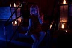 La bella donna con provocatorio compone il vestito misura breve rosso d'uso dallo zecchino che si siede sulle scale nel night-clu fotografia stock