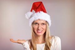 La bella donna con un cappello di Santa gestures la palma su Immagine Stock