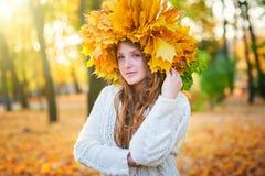 La bella donna con una corona di giallo lascia nel parco immagine stock libera da diritti