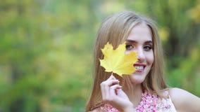La bella donna copre il suo fronte di foglie di acero gialle nel giorno di autunno nel parco archivi video