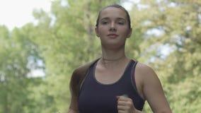 La bella donna dai capelli lunghi sicura funziona in attrezzatura di sport, movimento lento all'aperto archivi video