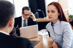 La bella donna dai capelli rossi ascolta attentamente l'uomo che esamina l'avvocato di divorzio fotografia stock libera da diritti
