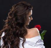 La bella donna del brunette che tiene il colore rosso è aumentato Immagine Stock Libera da Diritti