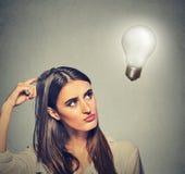 La bella donna della ragazza pensa cercando la lampadina della luce intensa fotografia stock