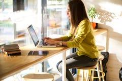 La bella donna di affari con capelli scuri ed il maglione giallo lavora nel coworking Fotografia Stock Libera da Diritti
