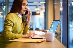 La bella donna di affari con capelli scuri ed il maglione giallo lavora nel coworking Immagine Stock Libera da Diritti