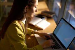 La bella donna di affari con capelli scuri ed il maglione giallo lavora nel coworking Fotografie Stock Libere da Diritti