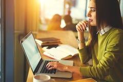La bella donna di affari con capelli scuri ed il maglione giallo lavora nel coworking collegato ad Internet senza fili nello spaz Fotografia Stock