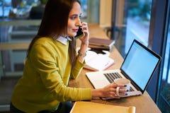La bella donna di affari con capelli scuri ed il maglione giallo lavora nel coworking collegato al collegamento senza fili alla r Fotografia Stock