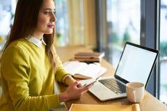 La bella donna di affari con capelli scuri ed il maglione giallo lavora nel coworking facendo uso dello smartphone moderno Fotografie Stock Libere da Diritti