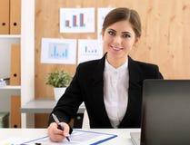 La bella donna di affari si siede nel luogo di lavoro nel lavoro d'ufficio con pappa Fotografia Stock