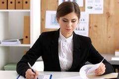 La bella donna di affari si siede nel luogo di lavoro in ufficio Fotografie Stock