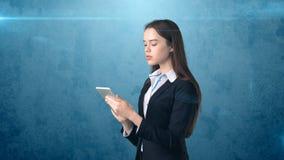 La bella donna di affari sta esaminando un cuscinetto di tocco, fondo blu Fotografia Stock