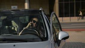 La bella donna di affari sta parlando sul telefono cellulare e sta sorridendo mentre si sedeva nella sua nuova automobile Poi sta video d archivio