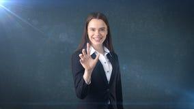 La bella donna di affari sta spingendo un bottone invisibile, fondo grigio Fotografia Stock