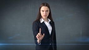La bella donna di affari sta spingendo un bottone invisibile, fondo grigio Fotografie Stock