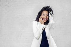 La bella donna di colore parla dal telefono cellulare in vestito bianco, muro di mattoni Immagine Stock Libera da Diritti