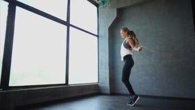 La bella donna di forma fisica che fa lo sport si esercita nella palestra archivi video