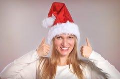 La bella donna di Natale con i pollici aumenta il segno Immagini Stock