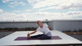 La bella donna di yoga sta sedendosi nel mezzo loto rilegato in avanti piega al rallentatore stock footage