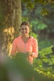 La bella donna durante la forma fisica al parco è musica d'ascolto immagine stock libera da diritti