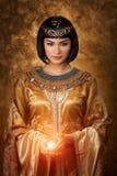 La bella donna egiziana gradisce Cleopatra con la palla magica su fondo dorato Fotografia Stock