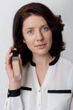 La bella donna elegante con trucco dimostra i prodotti cosmetici decorativi in barattoli per l'applicazione del trucco su un back Fotografie Stock Libere da Diritti