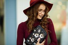La bella donna elegante sta indossando i vestiti ed i vetri di autunno di modo con la borsa nera, concetto di caduta Immagini Stock