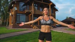 La bella donna esile in abiti sportivi sui precedenti della casa sul prato inglese esegue i salti per cardio addestramento e gras stock footage