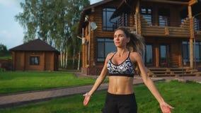 La bella donna esile in abiti sportivi sui precedenti della casa sul prato inglese esegue i salti per cardio addestramento e gras archivi video