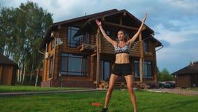 La bella donna esile in abiti sportivi sui precedenti della casa sul prato inglese esegue i salti per cardio addestramento e gras video d archivio