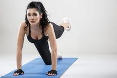 La bella donna esile che fa l'allungamento si esercita sull'isolante della stuoia di yoga Fotografia Stock