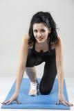 La bella donna esile che fa l'allungamento si esercita sull'isolante della stuoia di yoga Fotografie Stock
